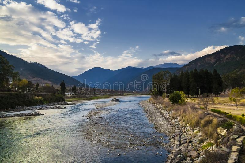 Mo Chhu River on a nice sunny day, Punakha, Bhutan. View from the wooden cantilever bridge near Punakha Dzong to river, houses of. Punakha city and Himalaya royalty free stock photos