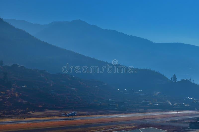 Paro flygplats i bergen - Bhutan Berglandskap med byn och kortkortflygplatsen E arkivfoton