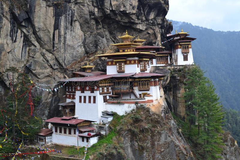 Paro Taktshang Tiger`s Nest Monastery perched on a cliff. Paro Taktshang Monastery is perched high on a precarious cliff. It bears a great significance to royalty free stock image