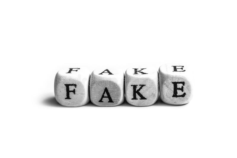 parola che si forma sulle lettere di legno su fondo bianco - concetto falso di notizie immagine stock