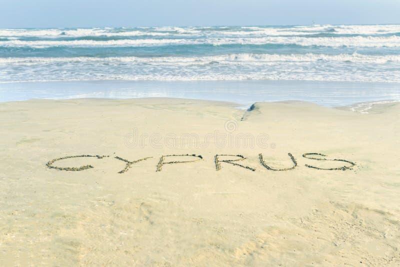 Parola Cipro sulla spiaggia sabbiosa bagnata del McKenzie a Larnaca Testo del paese di nome immagine stock libera da diritti