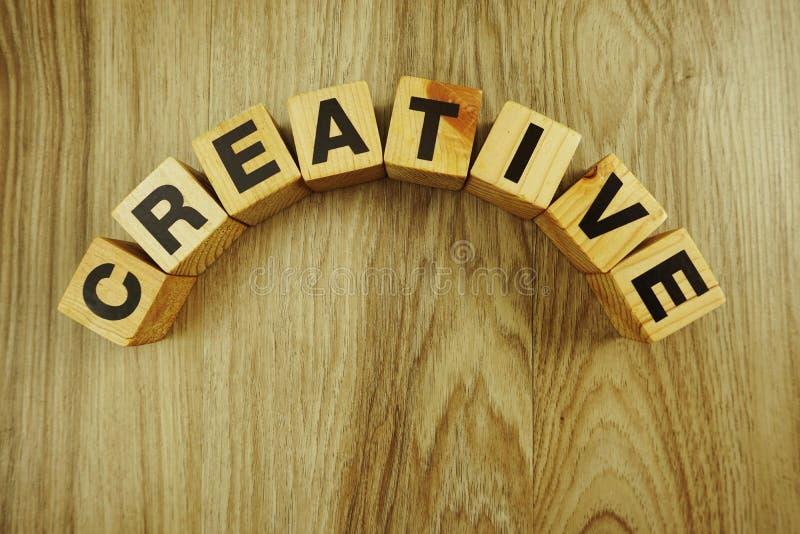 Parola creativa fatta dai cubi di legno con l'alfabeto delle lettere fotografia stock