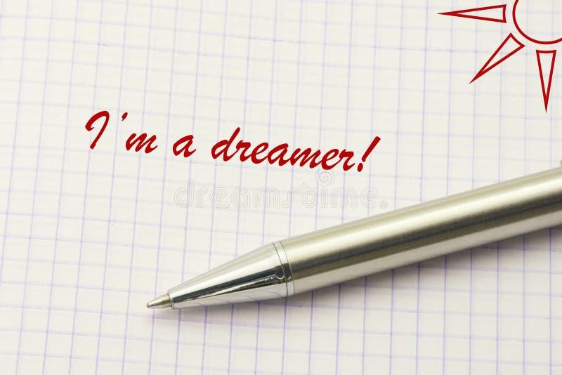 Parola del sognatore scritta su carta Sogno del concetto testuale con la penna dell'argento e del sole fotografia stock