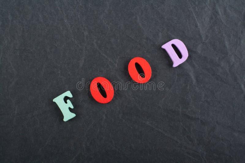 Parola dell'ALIMENTO sul fondo nero composto dalle lettere di legno di ABC del blocchetto variopinto di alfabeto, spazio del bord fotografie stock