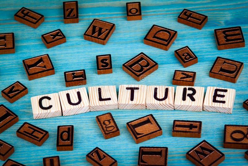 Parola della cultura scritta sul blocco di legno Alfabeto di legno su un fondo blu immagini stock
