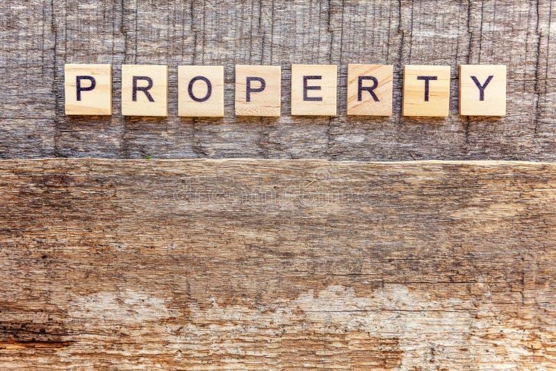 Parola delle lettere della PROPRIETÀ dell'iscrizione su fondo di legno immagini stock libere da diritti