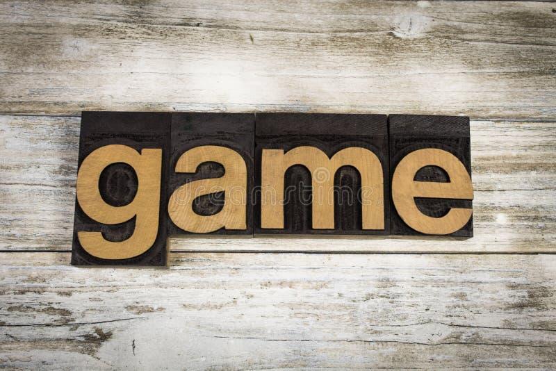 Parola dello scritto tipografico del gioco su fondo di legno immagini stock