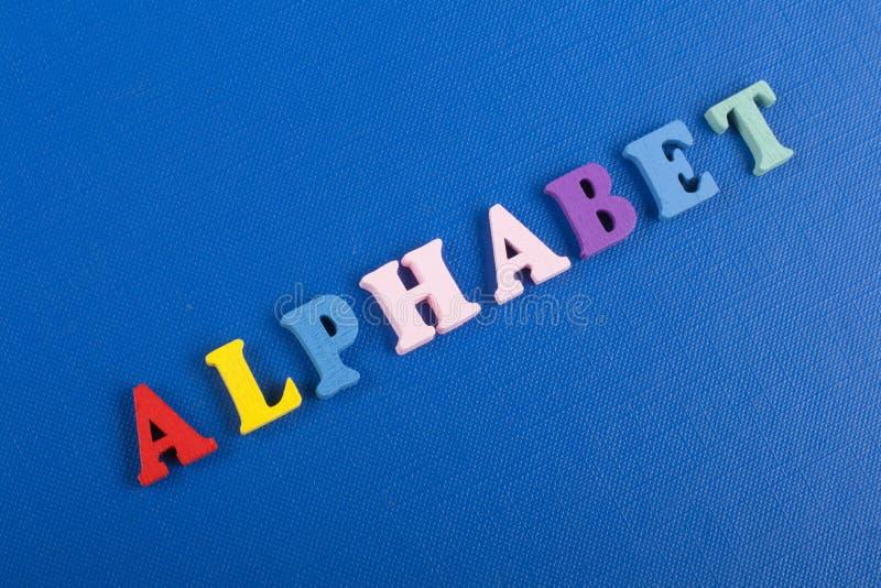 Parola di ALFABETO su fondo blu composto dalle lettere di legno di ABC del blocchetto variopinto di alfabeto, spazio della copia  fotografie stock