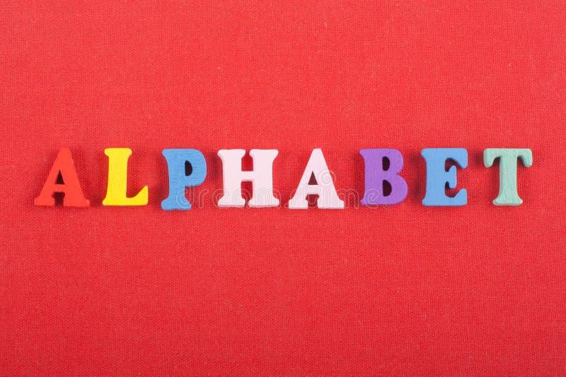 Parola di ALFABETO su fondo rosso composto dalle lettere di legno di ABC del blocchetto variopinto di alfabeto, spazio della copi fotografia stock libera da diritti