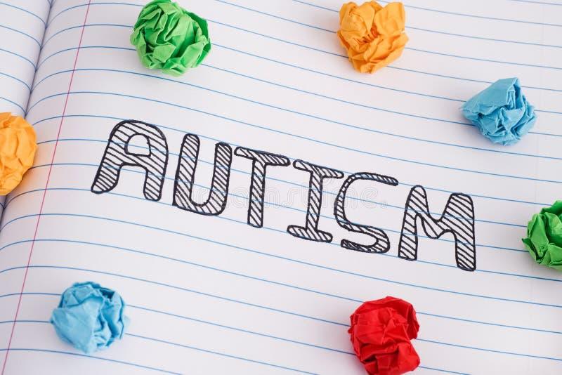 Parola di autismo sullo strato del taccuino con alcune palle di carta sgualcite variopinte su  immagini stock libere da diritti