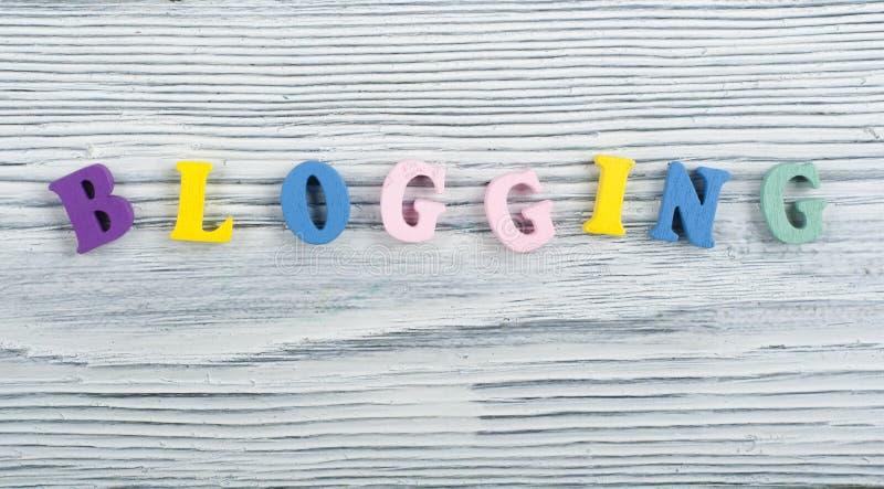 Parola di BLOGGING su fondo di legno composto dalle lettere di legno di ABC del blocchetto variopinto di alfabeto, spazio della c fotografie stock
