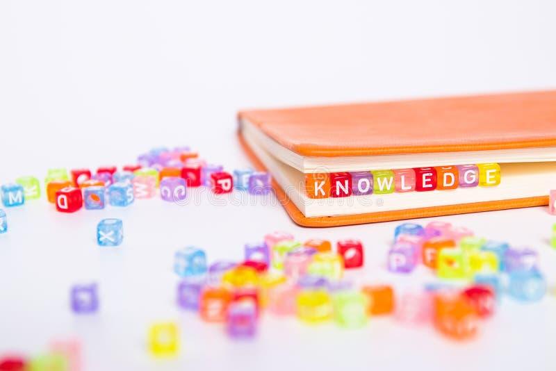 Parola di CONOSCENZA sul blocchetto variopinto della perla come segnalibro in libro Concetto di conoscenza e di formazione immagine stock