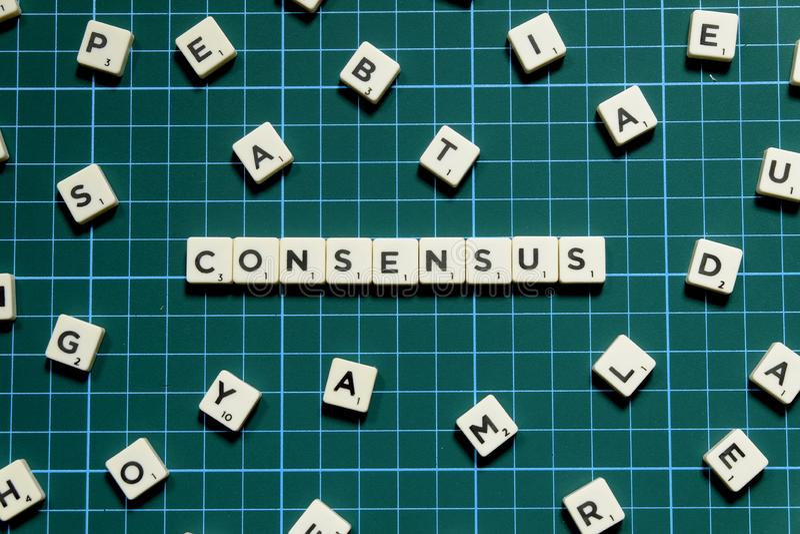 Parola di consenso fatta del blocchetto quadrato della lettera sul fondo quadrato verde della stuoia immagini stock