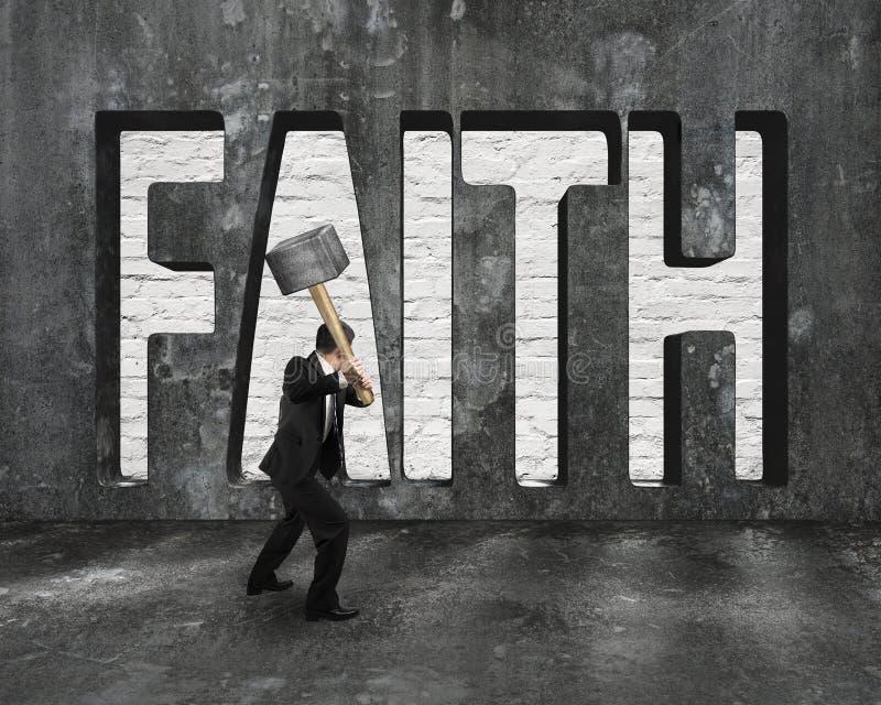Parola di fede sul muro di cemento con il martello della tenuta dell'uomo immagini stock libere da diritti