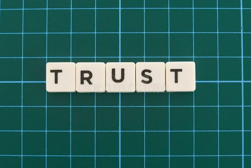 Parola di fiducia fatta della parola quadrata della lettera sul fondo quadrato verde della stuoia fotografia stock