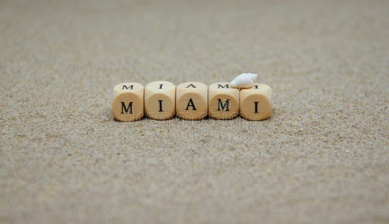 parola di Miami sviluppata con i cubi di legno e le lettere nere sul pavimento e sul fondo della spiaggia di sabbia fotografie stock libere da diritti