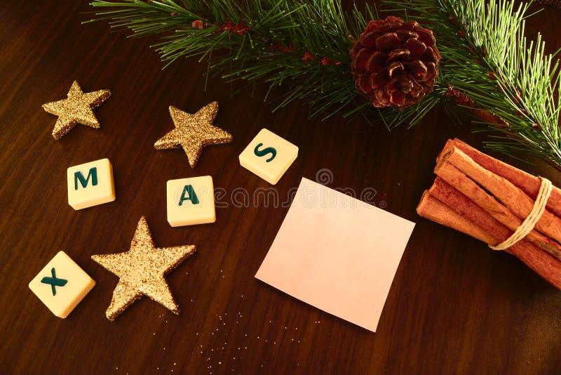 Parola di natale con Libro Bianco, la candela della torcia elettrica, la stella, il ramo del pino e la cannella immagine stock