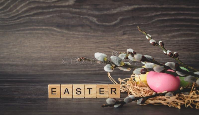 Parola di Pasqua delle compresse di legno leggere, ramoscelli del salice con le guarnizioni e fotografia stock