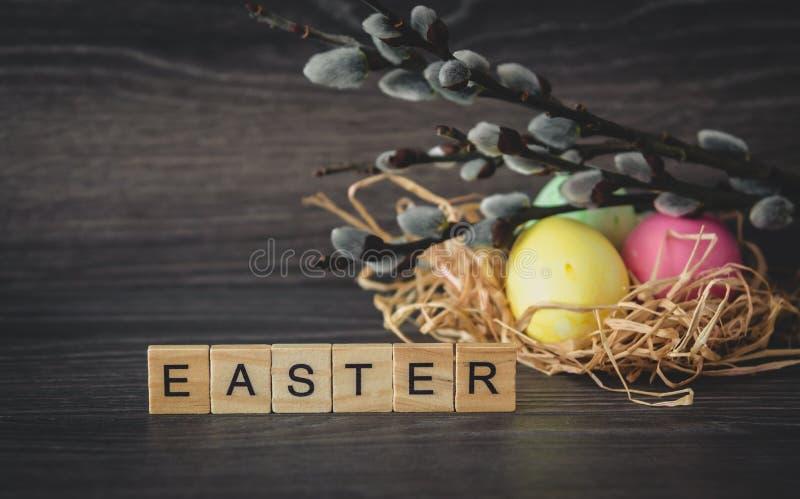 Parola di Pasqua delle compresse di legno leggere, ramoscelli del salice con le guarnizioni e immagini stock libere da diritti