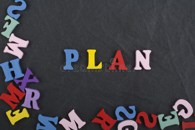 Parola di PIANO sul fondo nero composto dalle lettere di legno di ABC del blocchetto variopinto di alfabeto, spazio del bordo del immagine stock libera da diritti