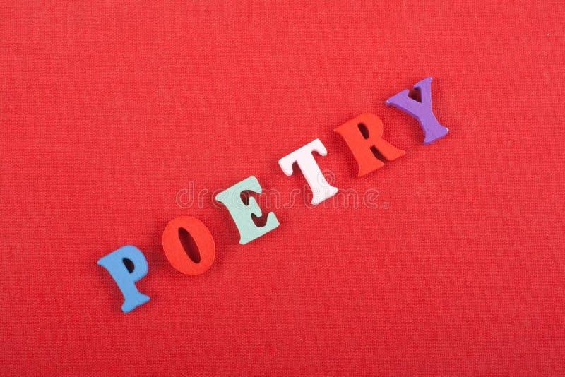 Parola di POESIA su fondo rosso composto dalle lettere di legno di ABC del blocchetto variopinto di alfabeto, spazio della copia  fotografia stock