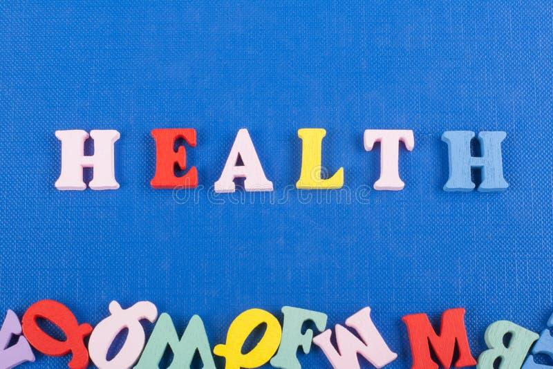 Parola di SALUTE su fondo blu composto dalle lettere di legno di ABC del blocchetto variopinto di alfabeto, spazio della copia pe fotografia stock libera da diritti