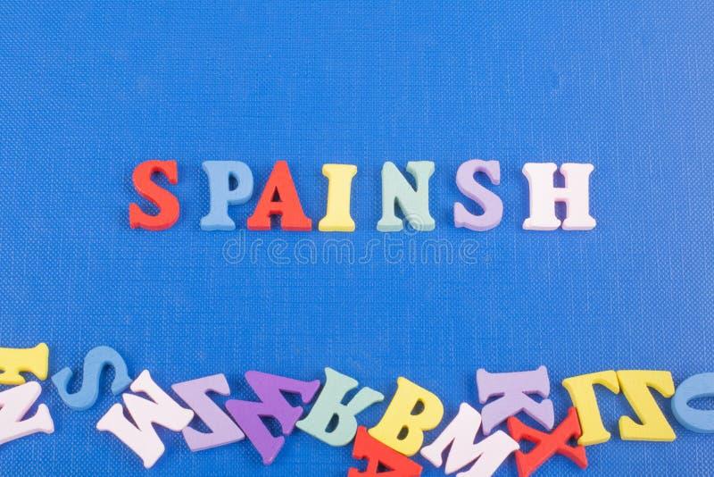 Parola di Spainsh su fondo blu composto dalle lettere di legno di ABC del blocchetto variopinto di alfabeto, spazio della copia p fotografie stock libere da diritti
