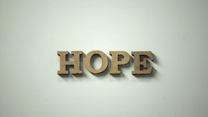 Parola di speranza fatta delle lettere di legno che si trovano sulla tavola, attesa del recupero, guarente immagini stock