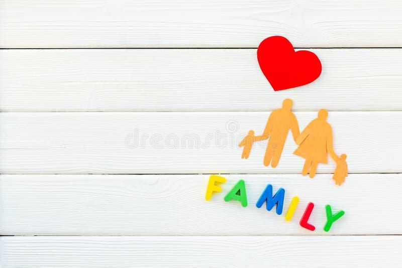 Parola e figura della famiglia per adottare concetto del bambino su derisione bianca di vista superiore del fondo su fotografia stock libera da diritti