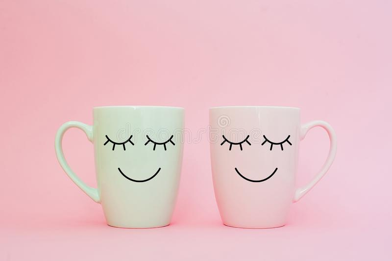 Parola felice di venerdì Due tazze di caffè stanno insieme per essere forma del cuore su fondo rosa con il fronte di sorriso sull fotografia stock libera da diritti