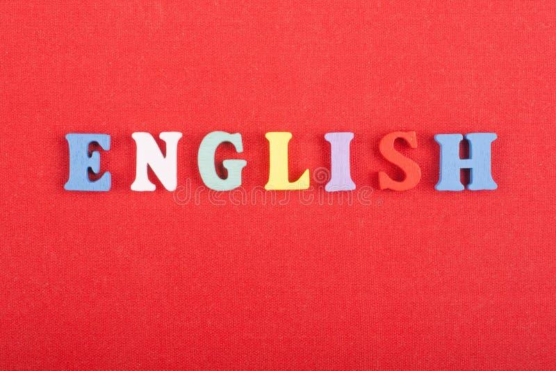 Parola inglese su fondo rosso composto dalle lettere di legno di ABC del blocchetto variopinto di alfabeto, spazio della copia pe fotografie stock libere da diritti