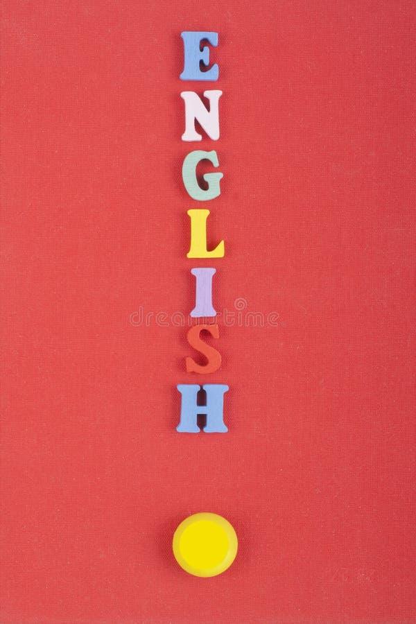 Parola inglese su fondo rosso composto dalle lettere di legno di ABC del blocchetto variopinto di alfabeto, spazio della copia pe fotografia stock