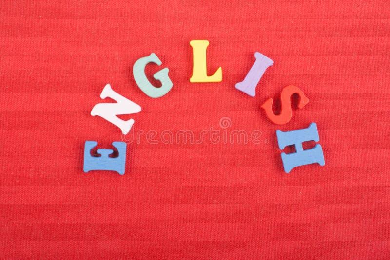 Parola inglese su fondo rosso composto dalle lettere di legno di ABC del blocchetto variopinto di alfabeto, spazio della copia pe fotografia stock libera da diritti