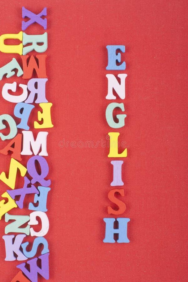 Parola inglese su fondo rosso composto dalle lettere di legno di ABC del blocchetto variopinto di alfabeto, spazio della copia pe fotografie stock