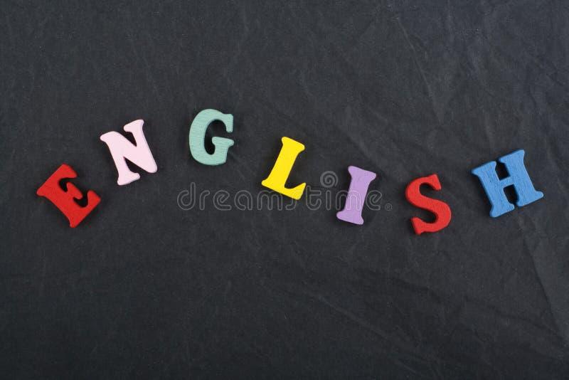 Parola inglese sul fondo nero composto dalle lettere di legno di ABC del blocchetto variopinto di alfabeto, spazio del bordo dell fotografie stock libere da diritti