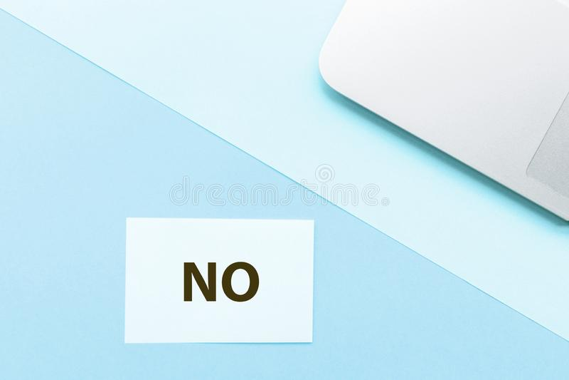 Parola nessuna e computer portatile su fondo blu Concetto creativo della cancelleria di minimalismo Vista superiore, disposizione immagine stock libera da diritti