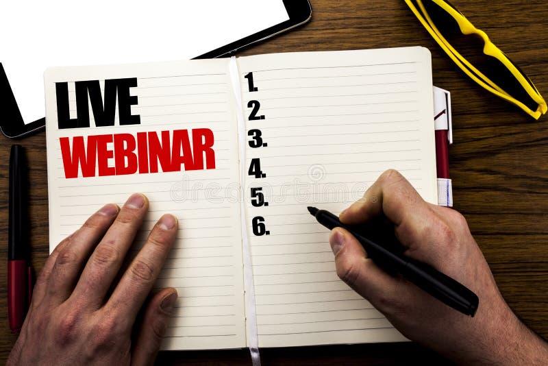 Parola, scrivente Live Webinar Concetto di affari per l'e-learning di web di affari scritto sul libro, fondo di legno con la mano fotografia stock libera da diritti