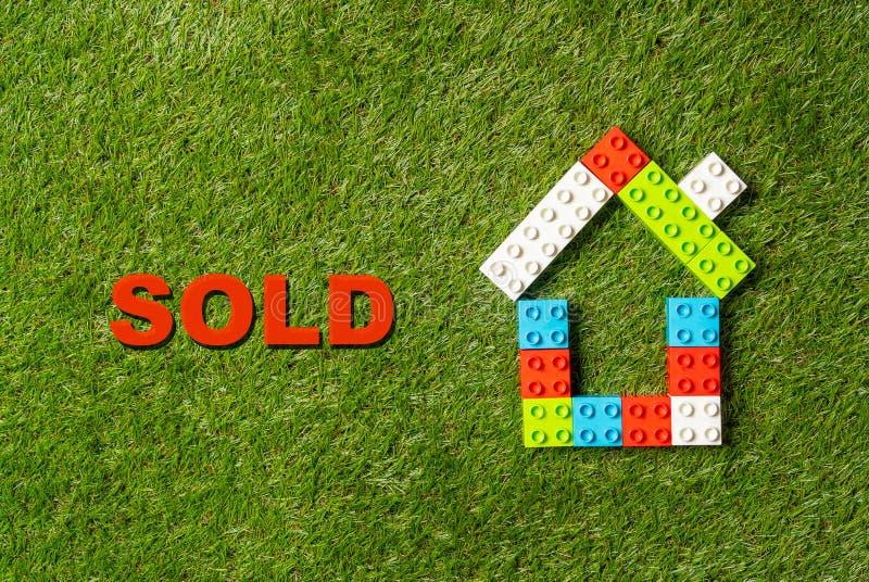 Parola variopinta Sold della casa dei blocchetti del giocattolo scritta su erba concetto in industria di proprietà e dello stato  fotografie stock