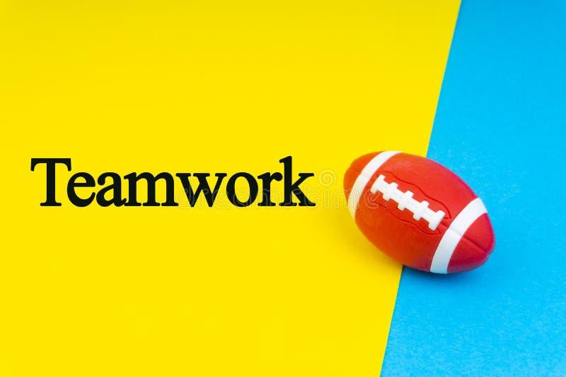 Parole di LAVORO DI SQUADRA scritte e palla di rugby su fondo blu e giallo illustrazione di stock