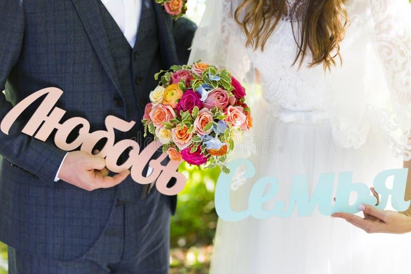 Parole di legno nel Russo in mani del mazzo della sposa e dello sposo e di nozze fotografie stock