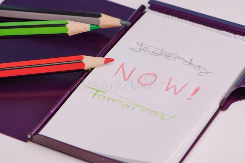 Parole scritte a mano: ieri, ora, domani su un blocco note bianco fotografia stock libera da diritti