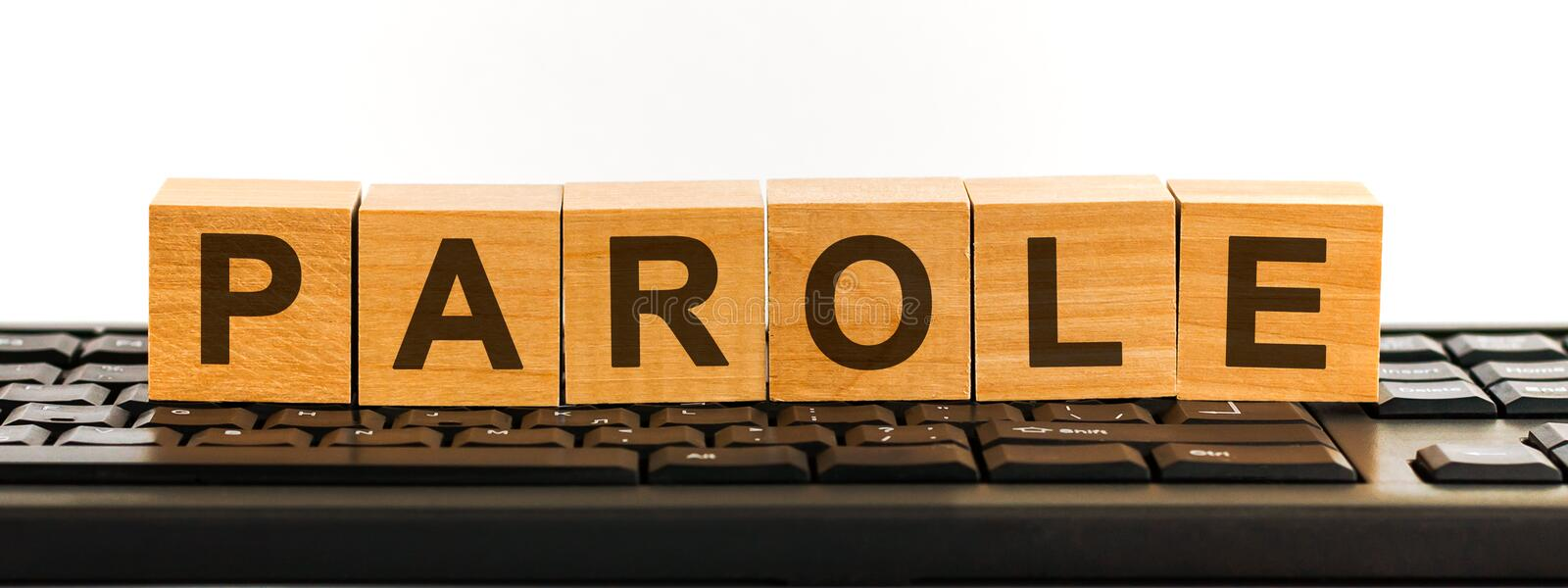 PAROLE word made with building blocks. A row of wooden cubes with a word written in black font is located on a black keyboard.  royalty free stock image