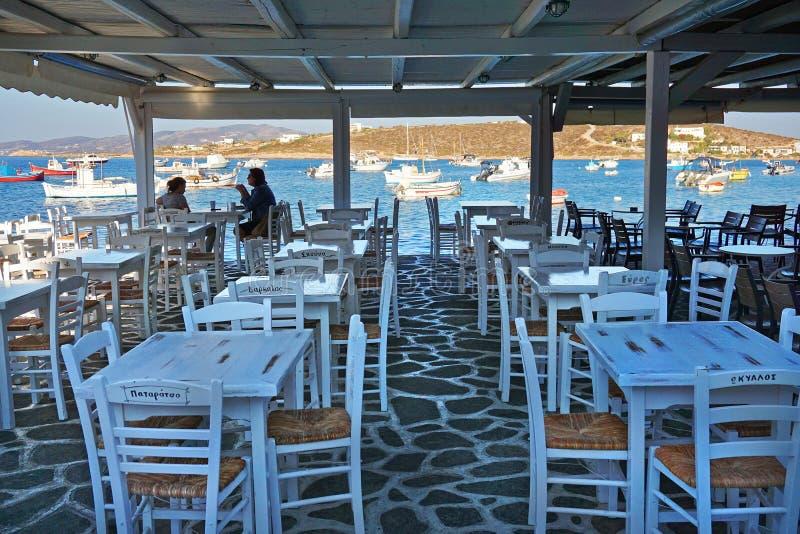 Paros Grekland SEPTEMBER 2018 första kunder för morgonkaffe i en stång på porten av Lefkes, Paros royaltyfria foton