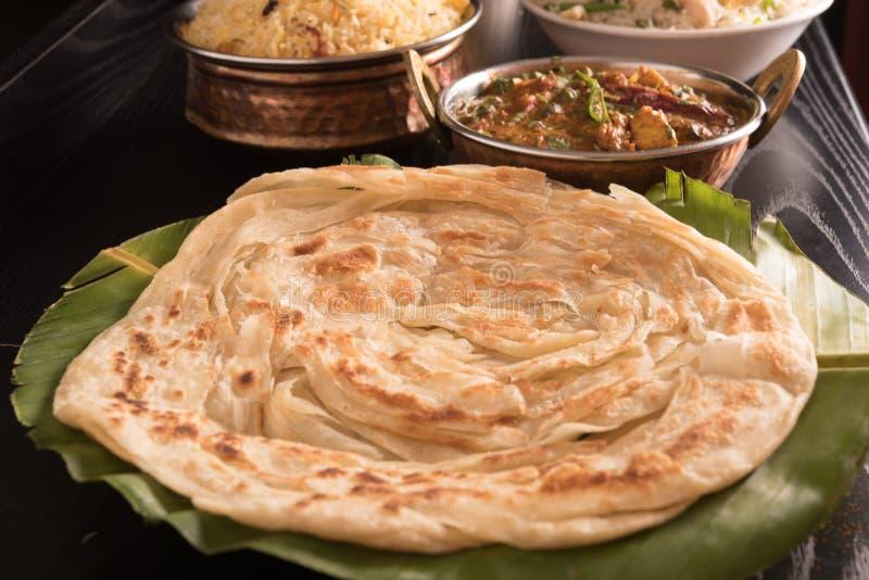 Parotta chaud sur la feuille de banane avec le biryani, le beurre Masala de Paneer et le riz frit photographie stock libre de droits