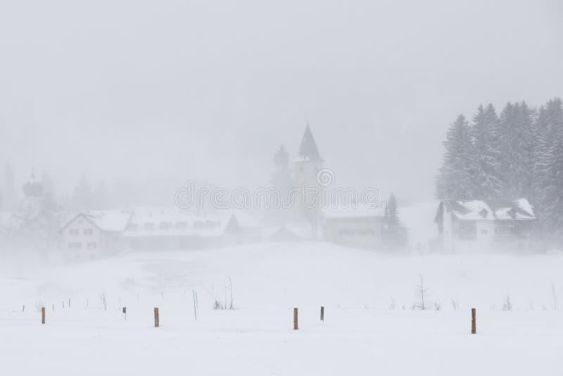 Parpan med kyrkan i snö royaltyfri foto