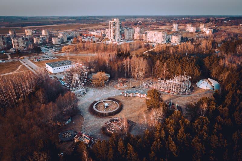 Parque abandonado do carrossel e panorama da cidade de Elektrenai Este parque abandonado está na cidade de Elektrenai em Lituânia imagem de stock