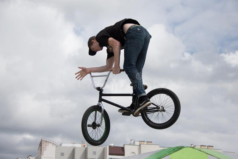 Parque central. Ciclismo extremo. Un hombre en una bicicleta deportiva da un salto peligroso fotos de archivo