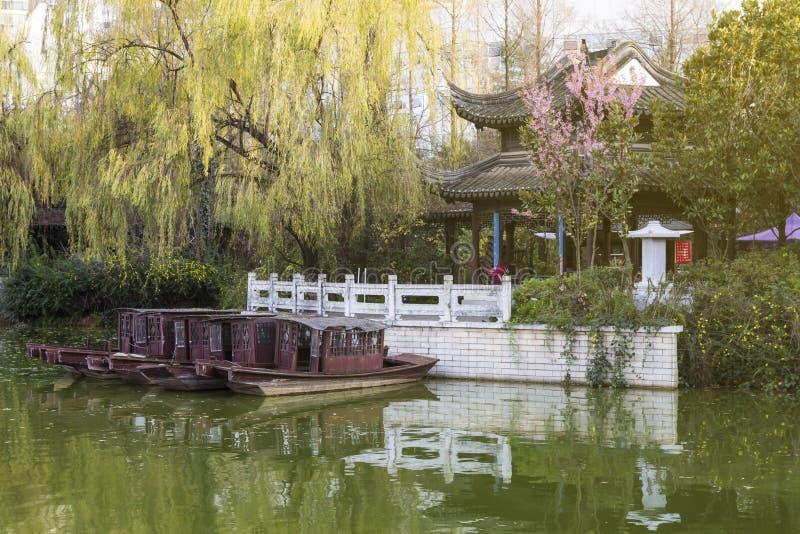 Parque chino típico con una charca y barcos en la ciudad de Kunming fotografía de archivo libre de regalías