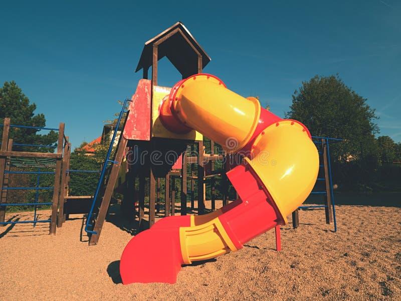 Parque colorido da corrediça do tubo do campo de jogos em público Tubo novo do slider e escadas de madeira fotografia de stock royalty free
