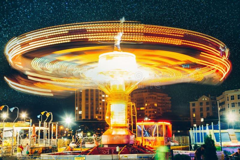 Parque de atracciones y carrusel en la noche, concepto largo del disfrute del carnaval del entretenimiento de la falta de definic imagenes de archivo